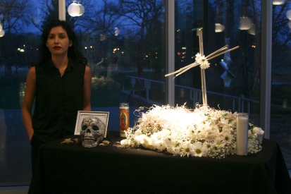 Karla Giguere standing next to the altar she created and installed for Day of the Dead Poets Slam 2015.